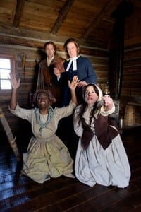 L-R, standing: J. Todd Adams (Reverend John Hale) and Fletcher McTaggart (John Proctor). L-R, kneeling: Stephanie Weeks (Tituba) and Madison Micucci (Abigail Williams). Photo by Alexander Weisman.