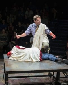Jeffrey Cummings as Marcus Brutus (squatting) and Paul Michael Sandberg as Julius Caesar (lying down) in the Utah Shakespeare Festival's 2016 production of Julius Caesar. (Photo by Katrina Christensen. Copyright Utah Shakespeare Festival 2016.)